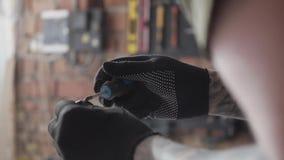 Eletricista farpado do close-up que trabalha com os detalhes que estão na tabela na garagem Um homem trabalha em uma oficina A pl filme
