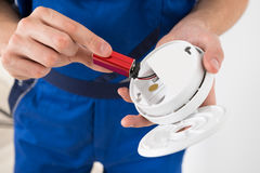Eletricista Holding Smoke Detector foto de stock royalty free