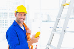 Eletricista masculino de sorriso que guarda o multímetro no escritório foto de stock royalty free