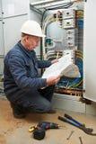 Eletricista na fiação com desenhos de funcionamento imagem de stock