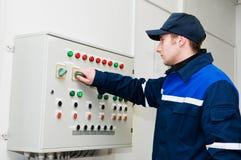 Eletricista no ajuste da tensão Foto de Stock