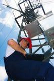 Eletricista no capacete vermelho que trabalha no polo da energia elétrica Foto de Stock Royalty Free