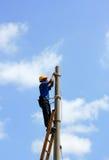 Eletricista no pólo elétrico da torre Fotografia de Stock Royalty Free