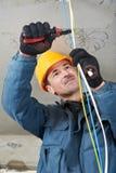 Eletricista no trabalho da fiação foto de stock