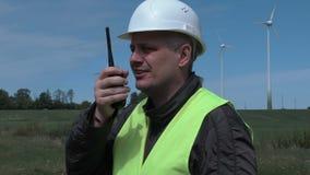 Eletricista no Walkietalkie perto das turbinas eólicas vídeos de arquivo