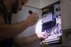 Eletricista novo com a lanterna elétrica perto da caixa de interruptor fotos de stock royalty free