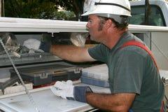Eletricista que alcanga no caminhão Fotos de Stock