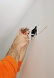 Eletricista que conecta a fiação durante a renovação da casa Fotografia de Stock