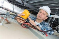 Eletricista que inspeciona fios inoperantes na parte superior do teto fotos de stock