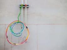 Eletricista que instala cabos distribuidores de corrente em uma construção nova Imagem de Stock