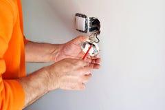Eletricista que instala interruptores bondes na casa nova Imagem de Stock