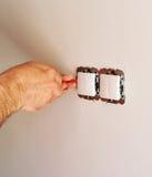 Eletricista que instala interruptores bondes na casa nova Imagem de Stock Royalty Free