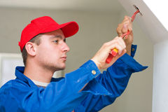 Eletricista que instala luzes Imagens de Stock