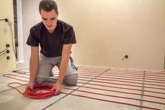 Eletricista que instala o fio vermelho de aquecimento do cabo elétrico no assoalho do cimento na sala inacabado Renovação e const imagens de stock royalty free