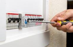 Eletricista que instala o fusível no painel com chave de fenda imagem de stock royalty free