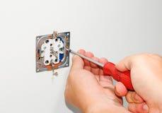 Eletricista que instala um soquete fixado na parede cinzento da alimentação CA com uma chave de fenda em uma parede branca, renov fotografia de stock