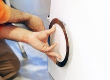 Eletricista que instala uma lâmpada moderna em uma chapa do emplastro para o teto da cozinha Foto de Stock Royalty Free