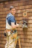 Eletricista que repara a luz ao ar livre Fotos de Stock Royalty Free