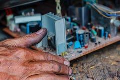 Eletricista que repara uma tevê na oficina de reparações velha da televisão imagem de stock