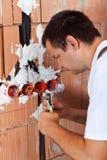 Eletricista que trabalha com fios em uma construção nova fotografia de stock