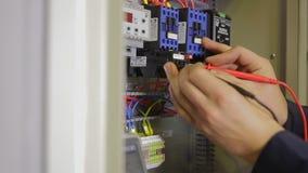 Eletricista que trabalha com interruptor, verificador, multímetro em uma caixa do fusível video estoque