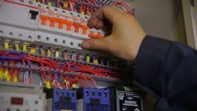 Eletricista que trabalha com interruptor, verificador, multímetro em uma caixa do fusível vídeos de arquivo