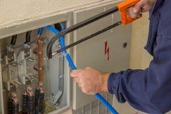Eletricista que trabalha com uma serra de cadeia no armário bonde 2 imagens de stock royalty free