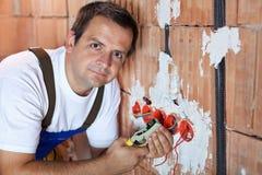 Eletricista que trabalha em uma construção nova imagens de stock royalty free