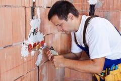 Eletricista que trabalha na instalação elétrica foto de stock