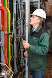 Eletricista que trabalha no chapéu duro com cabos Imagem de Stock