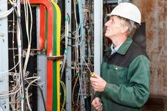 Eletricista que trabalha no chapéu duro com cabos Imagem de Stock Royalty Free
