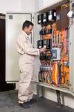 Eletricista que verific o circuito Fotografia de Stock