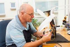 Eletricista superior que examina imagens de stock