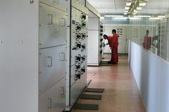 Eletricistas que inspecionam o equipamento na sala do painel de comando Fotografia de Stock Royalty Free