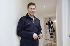 Eletricistas que instalam luzes de teto na casa doméstica foto de stock royalty free