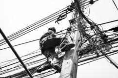 Eletricistas que reparam o fio no trabalho de escalada no polo de poder bonde do cargo Fotografia de Stock Royalty Free