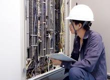Eletricistas que sorriem, inspecionando caixas elétricas na fábrica industrial imagens de stock