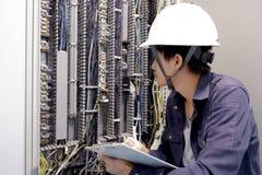 Eletricistas que sorriem, inspecionando caixas elétricas na fábrica industrial imagem de stock royalty free