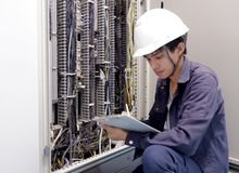 Eletricistas que sorriem, inspecionando caixas elétricas na fábrica industrial imagem de stock