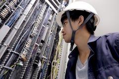 Eletricistas que sorriem, inspecionando caixas elétricas na fábrica industrial fotos de stock