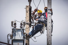 Eletricistas que trabalham no polo da eletricidade Imagens de Stock