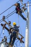 Eletricistas que trabalham no polo da eletricidade Fotografia de Stock Royalty Free