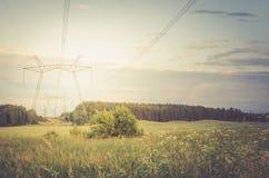 Eletro torres de alta tensão/eletro torres de alta tensão contra em um por do sol do fundo toned imagem de stock