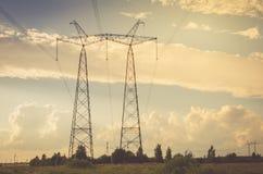 Eletro torres de alta tensão/eletro torres de alta tensão contra o por do sol imagens de stock royalty free