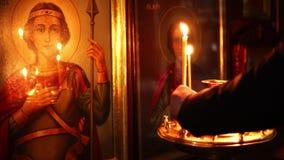 Elets,俄罗斯联邦- 2018年2月13日:人在宗教神圣前面的一个烛台投入一个蜡烛 影视素材