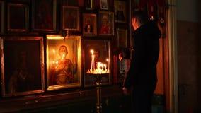 Elets, Fédération de Russie - 13 février 2018 : Un homme baptisé devant des icônes dans l'église orthodoxe à la lumière de clips vidéos