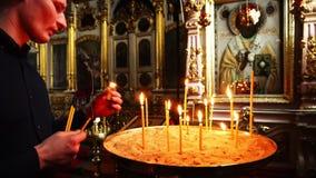 Elets, Russische Federatie - 2 April, 2018: Een mens dooft de kaarsen in de Kerk stock videobeelden
