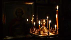 Elets, Russische Federatie - 2 April, 2018: Videoclose-up in de binnen Kerk Camerapan Brandende kaarsen op een gouden rek stock video