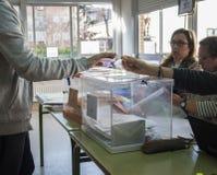 Elettore che mostra la sua carta di identità accanto alle urne elettorali al giorno delle elezioni generale spagnolo a Madrid, Sp Immagine Stock