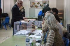 Elettore che presenta busta dentro l'urna al collegio elettorale per le elezioni generali spagnole a Madrid, Spagna Fotografie Stock Libere da Diritti